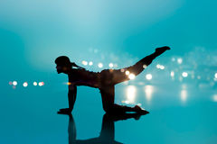 Woman yoga silhouette exercise on abstract blue floor background Stock Photography