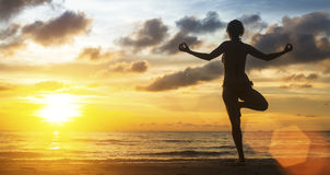 Woman yoga silhouette meditating on the ocean beach at amazing sunset. Royalty Free Stock Photo