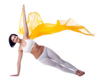Woman yoga stand on hand and yellow flying fabric Stock Images