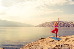 Woman in yoga tree pose meditating at the sea and mountains Royalty Free Stock Photography