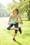 Woman in yoga tree pose. Smiling female fitness instructor doing yoga tree pose in green park Royalty Free Stock Image