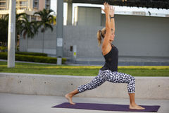 Woman in a yoga warrior pose Royalty Free Stock Images