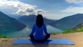 Woman yogi in mountain area. Back view girl meditating on the top of mountain area amazing view on the skyline with clouds and blue water stock footage