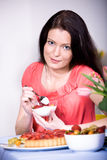 Woman with yogurt bowl. A young woman eating yogurt in the kitchen Royalty Free Stock Photography
