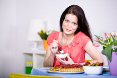 Woman with yogurt bowl. A young woman eating yogurt in the kitchen Royalty Free Stock Images