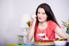 Woman with yogurt bowl. A young woman eating yogurt in the kitchen Stock Photography