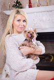 Woman with yorkshire terrier near fireplace Stock Photo