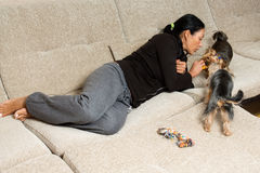 Woman - yorkshire terrier owner laying on the sofa with two dog Stock Photography