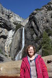Woman at Yosemite Falls California USA. A middle-aged Caucasian woman stands in front of the lower Yosemite Falls in Yosemite National Park, California USA, on a royalty free stock photo