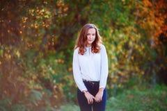 15 woman young Τοποθέτηση κοριτσιών χαμόγελου όμορφη στο ζωηρόχρωμο πάρκο φθινοπώρου Στοκ φωτογραφία με δικαίωμα ελεύθερης χρήσης
