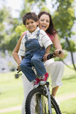 Woman and young boy on a bike outdoors smiling. At camera Royalty Free Stock Photos