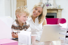 Woman and young boy in home office with laptop Royalty Free Stock Images