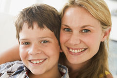 Woman and young boy in living room smiling. Close up of a woman and young boy in living room smiling at camera Royalty Free Stock Photo