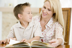 Woman and young boy reading book in dining room Royalty Free Stock Images