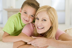 Woman and young boy sitting in living room smiling. Close up of woman and young boy sitting in living room smiling Royalty Free Stock Images
