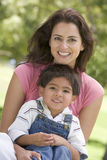 Woman and young boy sitting outdoors smiling Royalty Free Stock Image