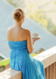 Young woman drinking coffee on morning terrace Stock Photography