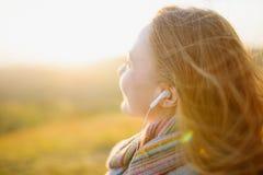 Young woman enjoying a music in the fall season. Autumn outdoor portrait Stock Photos