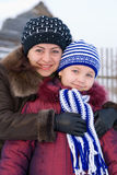 Woman with a young girl. In a cap and scarf Royalty Free Stock Image