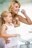 Woman and young girl in bathroom brushing teeth Stock Photos