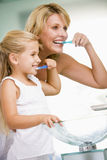 Woman and young girl in bathroom brushing teeth Stock Images