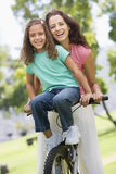 Woman and young girl on a bike outdoors smiling. At camera Stock Images
