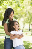 Woman and young girl  embracing and smiling Stock Photos