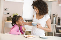 Woman and young girl in kitchen with cookies and c Royalty Free Stock Photos