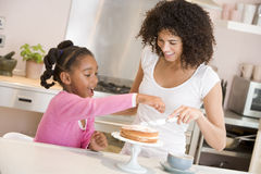 Woman and young girl in kitchen icing a cake smili Stock Photography