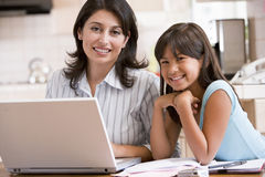Woman and young girl in kitchen with laptop Stock Photography