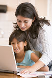 Woman and young girl in kitchen with laptop Stock Photos