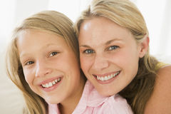 Woman and young girl in living room smiling. Close up of woman and young girl in living room smiling at camera Royalty Free Stock Photos