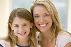 Woman and young girl in living room smiling. At camera Royalty Free Stock Photo