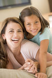 Woman and young girl in living room smiling. At camera Stock Photos