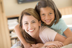 Woman and young girl in living room smiling. At camera Stock Photo