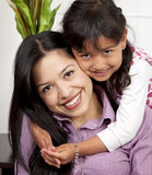 Woman and young girl in living room. Smiling Stock Photo