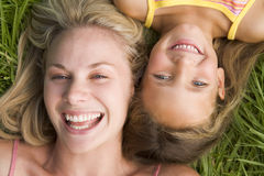Woman and young girl lying in grass laughing Royalty Free Stock Photo