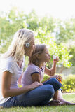 Woman and young girl outdoors blowing bubbles. Smiling Stock Image