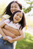 Woman and young girl outdoors embracing Stock Images