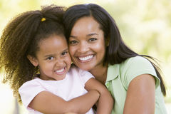 Woman and young girl outdoors embracing. And smiling royalty free stock images