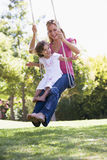Woman and young girl outdoors on tree swing. Smiling Stock Images