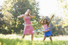 Woman and young girl outdoors using hula hoops stock image