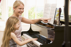 Woman and young girl playing piano and smiling Stock Photo