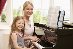 Woman and young girl playing piano and smiling. At camera royalty free stock image