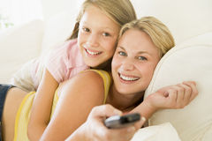 Woman and young girl with remote control. Embracing Stock Images
