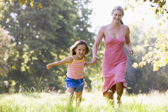 Woman and young girl running holding hands Stock Images