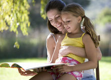 A woman and young girl sitting in the garden reading a book Royalty Free Stock Photography