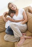 Woman and young girl sitting in living room Stock Photo