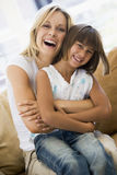Woman and young girl sitting in living room. Smiling Royalty Free Stock Photos