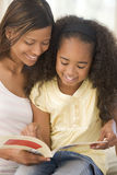 Woman and young girl sitting in living room stock photography